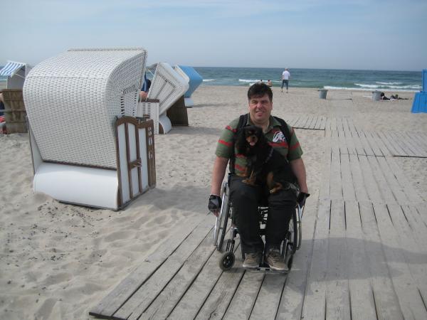 ala im Rollstuhl mit Hund auf dem Schoss am Strand von Warnemünde / Ostsee
