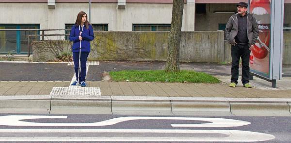Frau mit Blindenstock wartet an barrierefreier Bushaltestelle